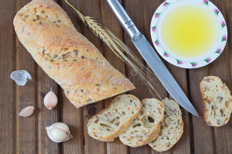 La ramita del cuchillo de pan, del aceite vegetal, del ajo y de la cebada fotos de archivo