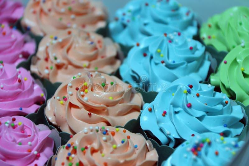La rangée d'orange, de bleu, de vert et de rose du gâteau de tasse avec du sucre arrondi coloré perle sur la crème photographie stock
