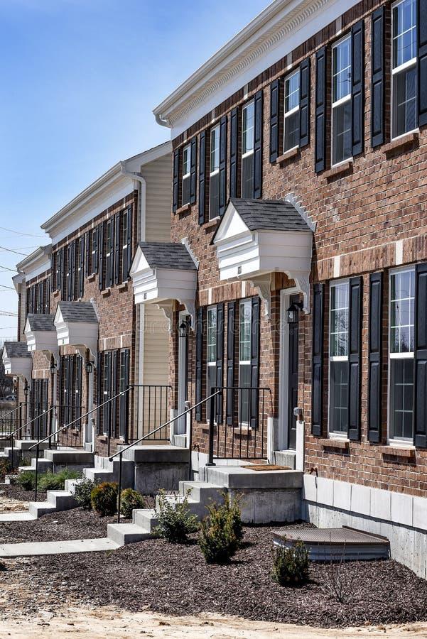 La rangée de la nouvelle brique jointe autoguide dans la subdivision nouvellement construite avec des volets et des étapes avant images stock