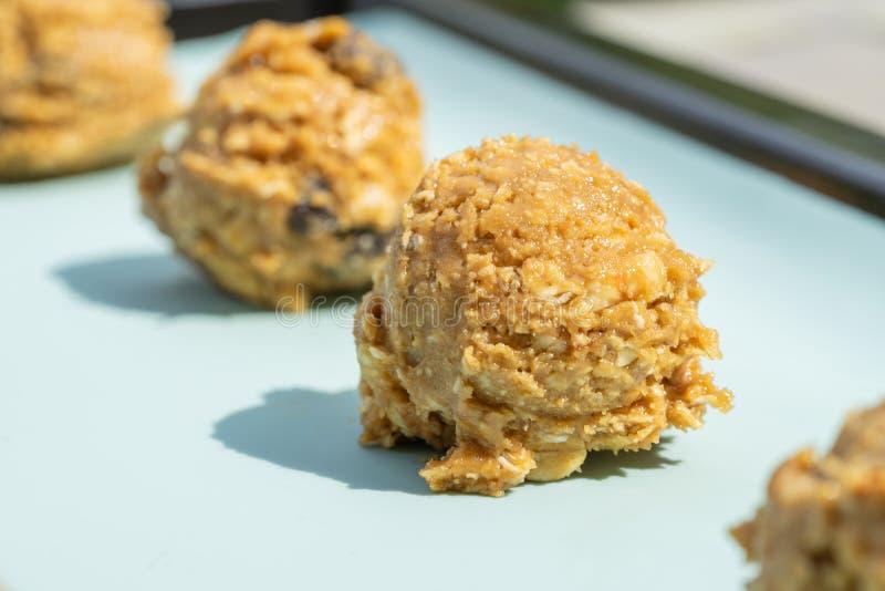 La rangée de la pâte naturelle de biscuit sur la plaque de cuisson, les noisettes brunes, le raisin sec et la farine d'avoine a m photo libre de droits