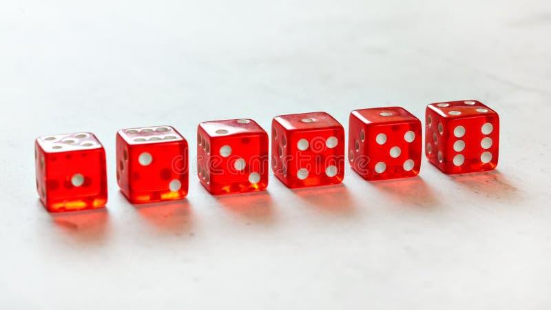 La rangée des merdes translucides rouges découpe montrer tous les nombres d'un à six, sur le conseil blanc photos libres de droits
