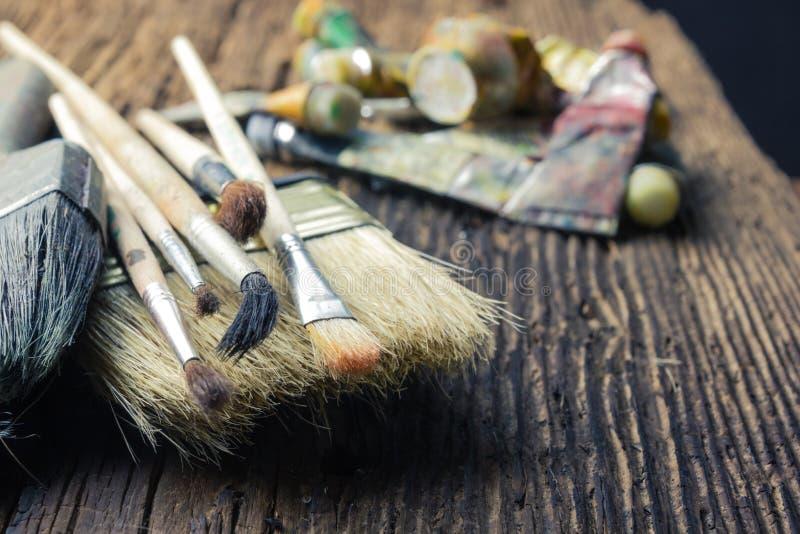 La rangée des pinceaux d'artiste se ferment sur le vieux grunge rustique naturel images stock