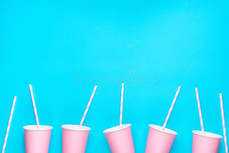 La rangée des tasses de papier vides roses a barré les pailles à boire disposées en frontière inférieure sur le fond bleu Configu image stock