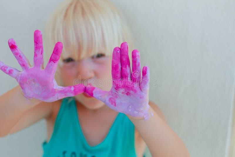La rappresentazione bionda sveglia della ragazza del bambino ha dipinto le mani viola e di rosa fotografie stock