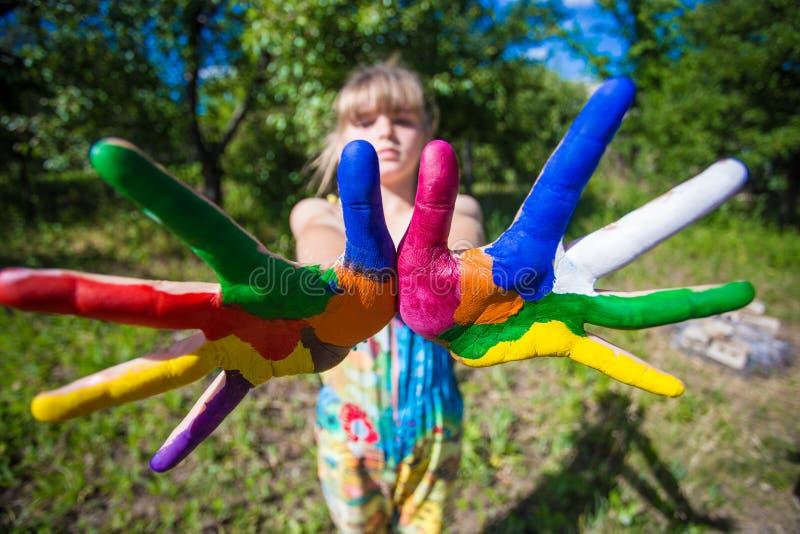 La rappresentazione della bambina ha dipinto le mani, fuoco sulle mani Mani verniciate bianche ambulanti fotografia stock libera da diritti