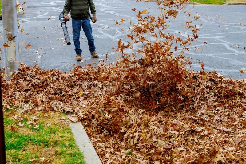 La rastrellatura della caduta va con le foglie di autunno del rastrello su pavimentazione e sulla scopa fotografia stock libera da diritti