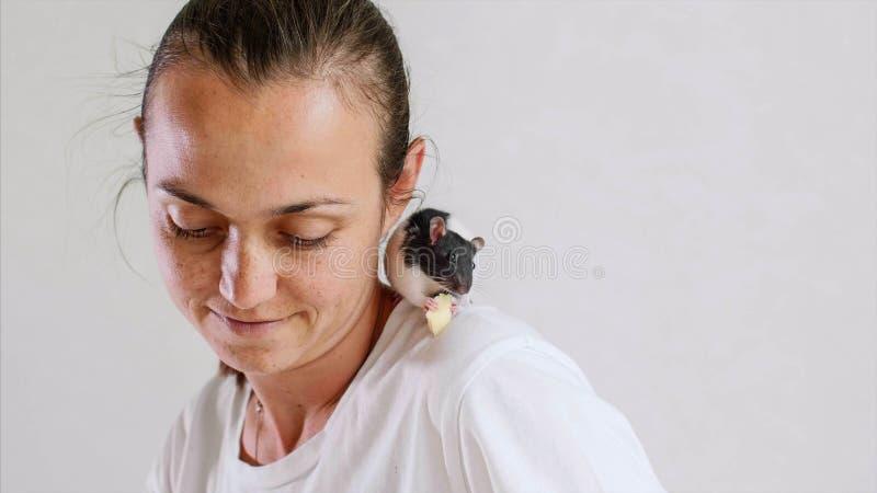 La rata de la mujer joven y del animal doméstico que se sienta en su hombro está desayunando junto imagen de archivo