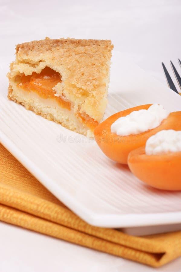 La rebanada de tarta del albaricoque sirvió en una placa blanca imagen de archivo