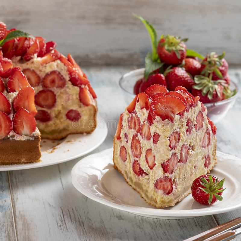 La rebanada de torta de la fresa con crema de la vainilla adornó con las fresas y la menta frescas imagenes de archivo