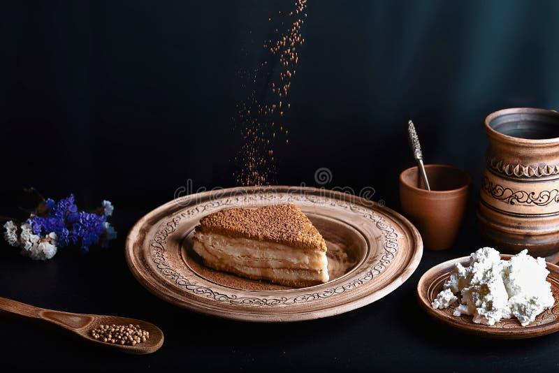 La rebanada de torta de miel vertida con la crema en una placa del vintage de la arcilla, cocinero del queso asperja con el cacao imagen de archivo libre de regalías
