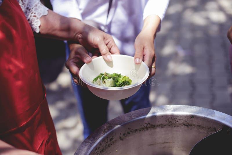 La recessione causa le penurie alimentari: Doni l'alimento con amore e speranza al povero: Il concetto di alimento è essenziale a fotografie stock