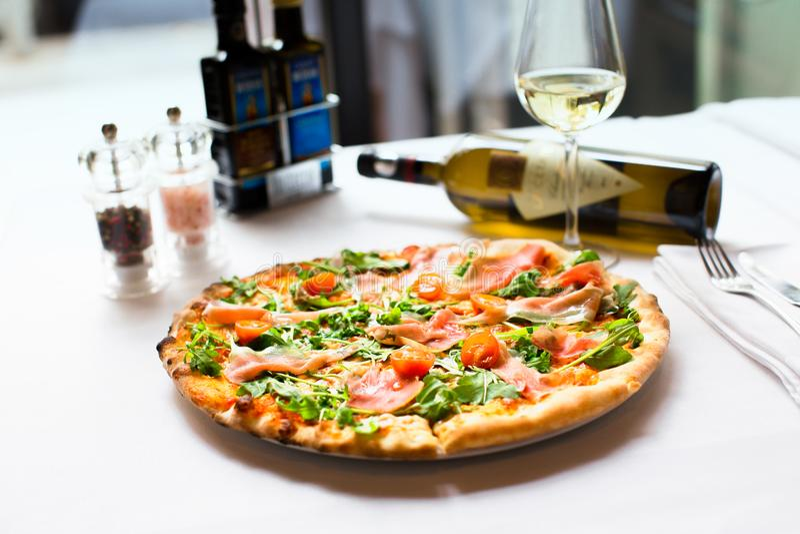 La recette délicieuse de pizza de saumons fumés a servi avec le bott de vin blanc photos stock