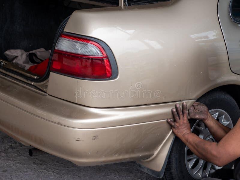 La recomprobación del mecánico quita el tope de un coche para hacer un nuevo dolor fotografía de archivo