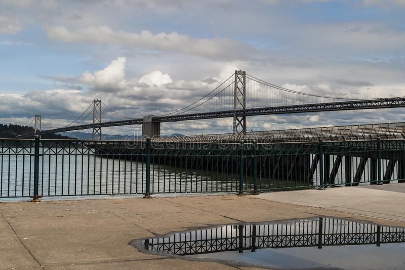 La reflexión de Bridgesde la bahía de San Francisco - de Oakland en un charco fotografía de archivo libre de regalías