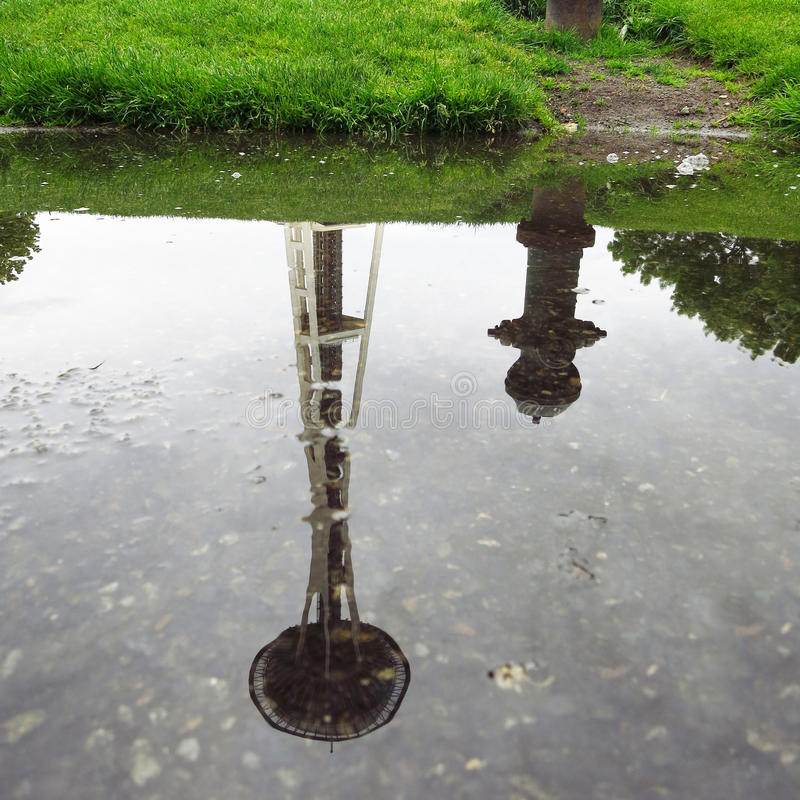 La reflexión de la aguja del espacio con agua cae día lluvioso imagenes de archivo