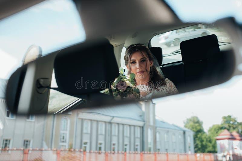 La reflexión de la novia en el espejo retrovisor del coche imagen de archivo libre de regalías