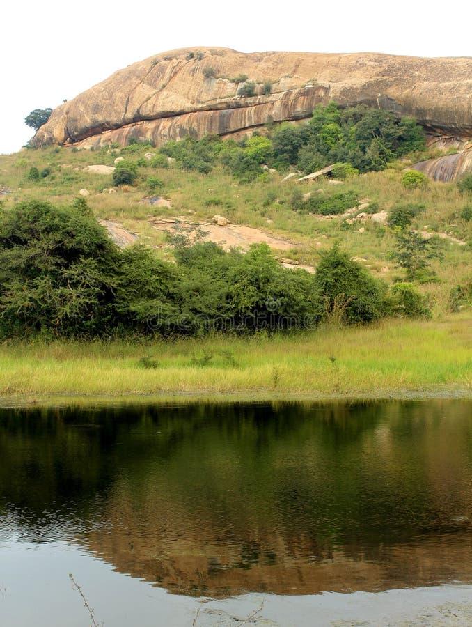 La reflexión hermosa de la colina en la piscina en el complejo sittanavasal del templo de la cueva fotos de archivo libres de regalías