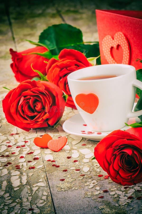 La regolazione del biglietto di S. Valentino della st con la tazza e le rose rosse di caffè immagini stock libere da diritti