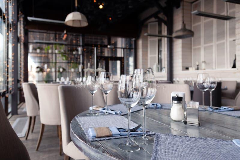 La regolazione del ristorante, il vino ed i tubi di livello, le forcelle ed i coltelli interni e moderni sui tovaglioli del tessu fotografia stock libera da diritti