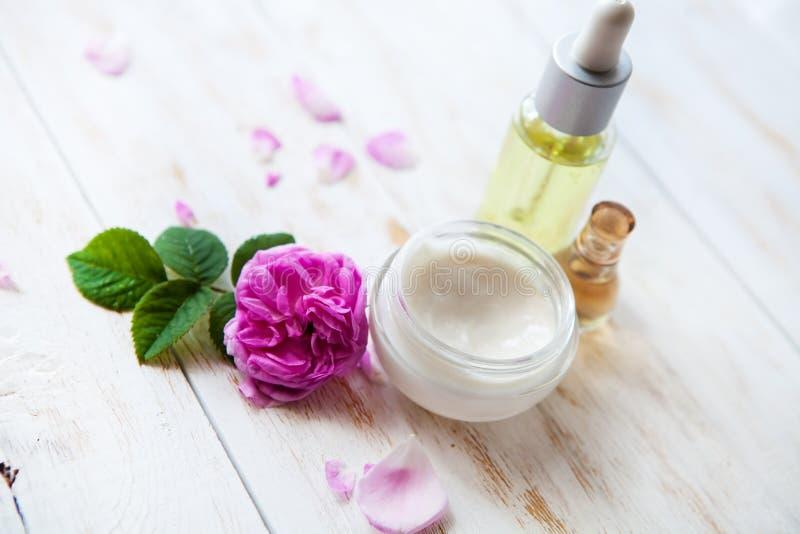 La regolazione della stazione termale con il vaso rose rosa d'idratazione della crema di fronte di belle e l'essenza rosa lubrifi fotografie stock