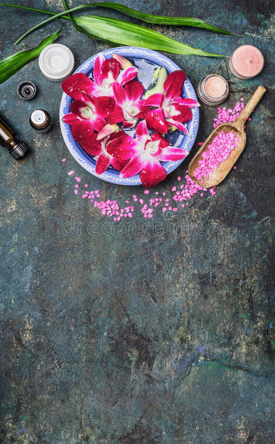 La regolazione della stazione termale con le ciotole dell'acqua, i fiori rosa dell'orchidea, il sale marino, la crema cosmetica e fotografia stock libera da diritti