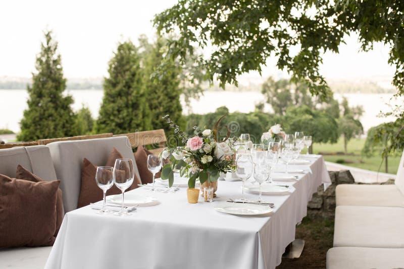 La regolazione della tavola di nozze ha decorato con i fiori freschi in un vaso d'ottone Nozze floristry Tavola di banchetto per  immagine stock