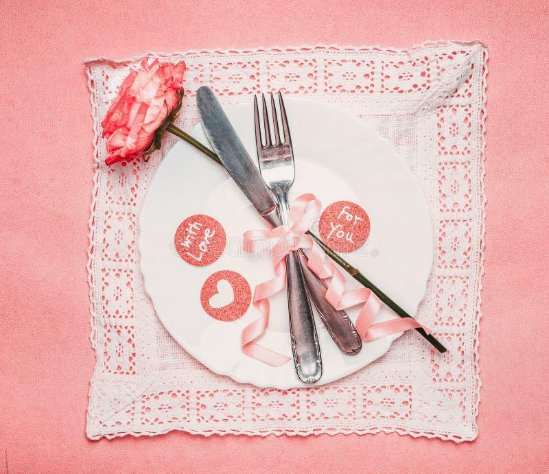 La regolazione di posto romantica della tavola con il piatto, è aumentato, coltelleria e nastro su fondo pallido rosa fotografia stock libera da diritti