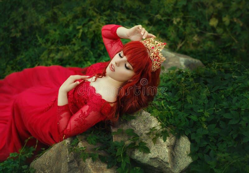 La reina en un vestido lujoso, costoso, rojo, con un tren largo miente en los matorrales de la hiedra Muchacha pelirroja en un or imágenes de archivo libres de regalías