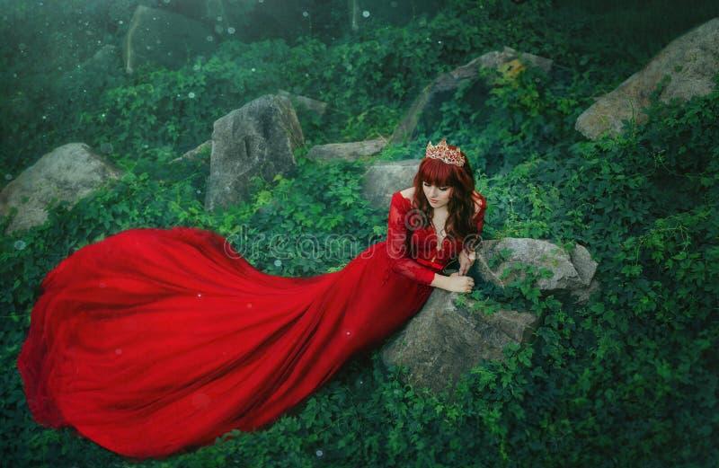 La reina en un vestido lujoso, costoso, rojo, con un tren largo miente en los matorrales de la hiedra Muchacha pelirroja en un or fotografía de archivo