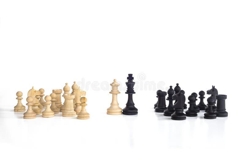 La reine blanche et le roi noir, traditionnellement confrontés dans le jeu d'échecs, sont ensemble Image à l'arrière-plan blanc d photos stock