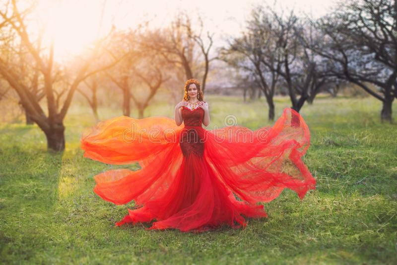La reine orientale dans une robe rouge est une silhouette d'une sirène avec un long train qui flotte dans le vent ?l?gant images stock
