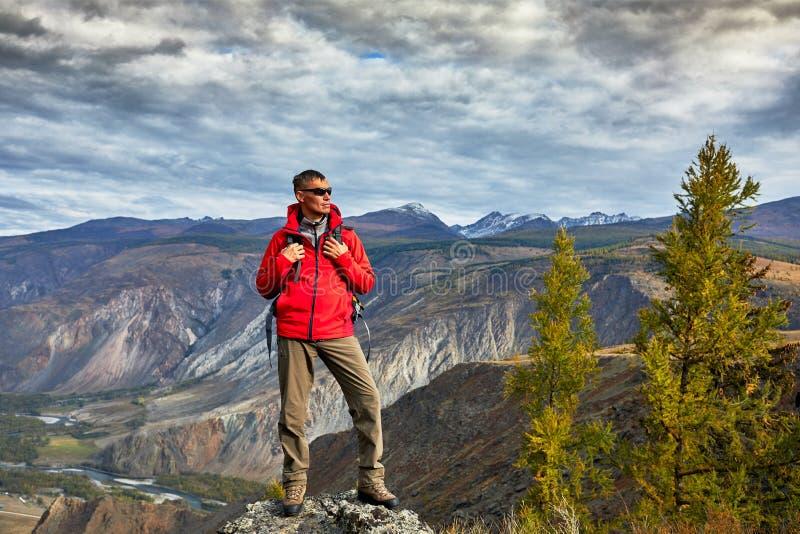La relajación del viajero del hombre joven al aire libre con las montañas rocosas de la mochila el otoño del fondo vacations y fo foto de archivo libre de regalías