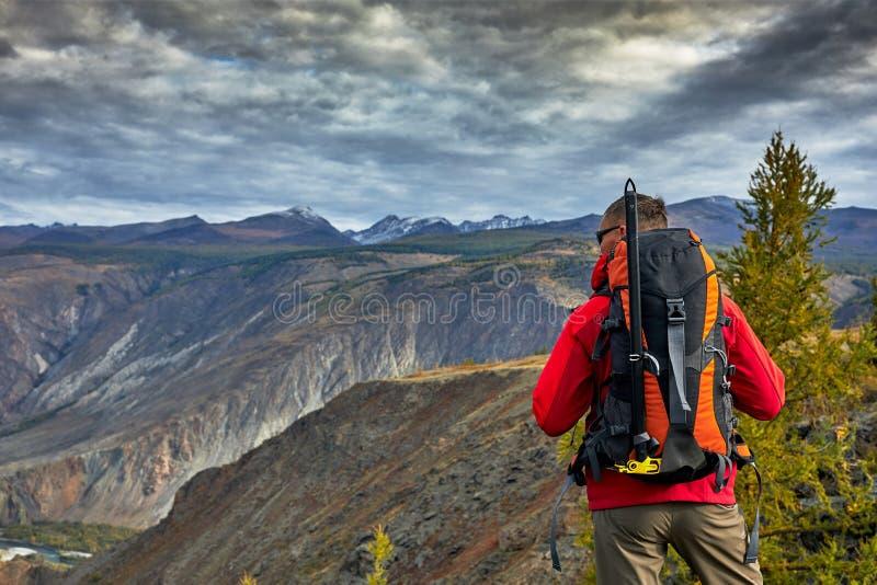 La relajación del viajero del hombre joven al aire libre con las montañas rocosas el otoño del fondo vacations y forma de vida imagenes de archivo