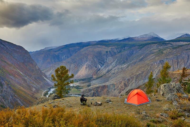 La relajación del viajero del hombre joven al aire libre con las montañas rocosas el otoño del fondo vacations y forma de vida imágenes de archivo libres de regalías