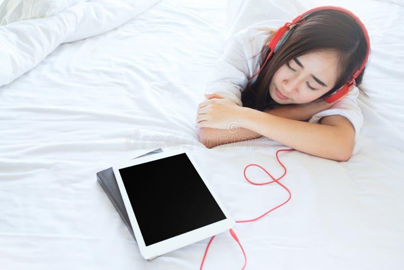 La relajación y escucha la música en cama en dormitorio fotografía de archivo libre de regalías