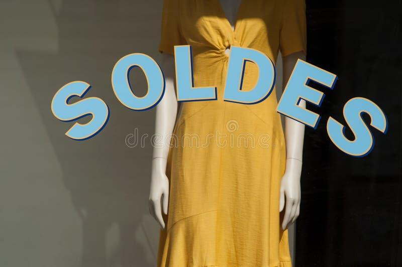 La remise se connectent la fenêtre dans la salle d'exposition française de magasin de mode sur le fond jaune de robe d'été photographie stock