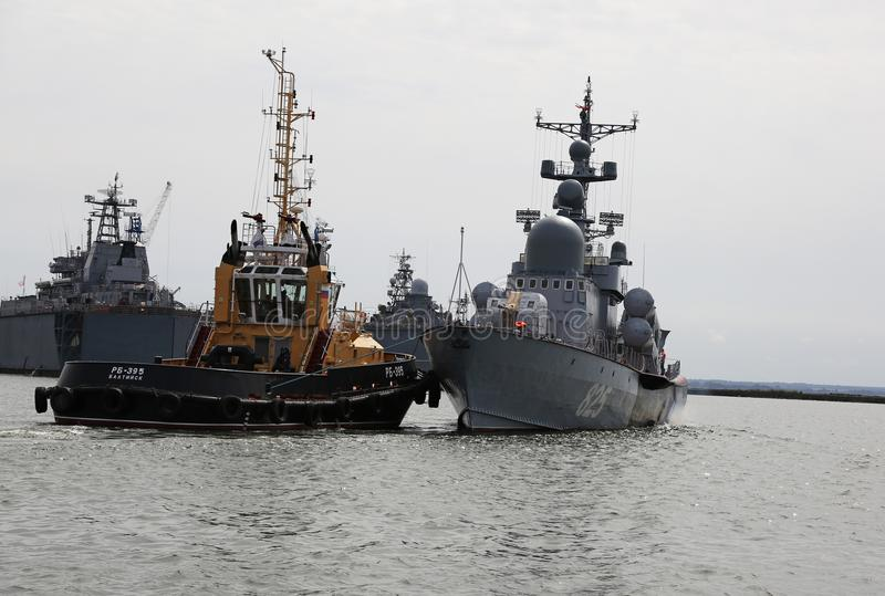 La remolque empuja el buque de guerra en el área del agua del puerto de Baltiysk fotografía de archivo