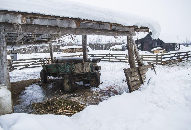 La remorque de ferme se tient sous un auvent en hiver photos libres de droits