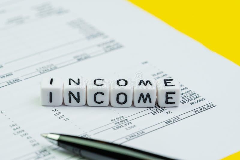 La renta, los ingresos de la compañía o el concepto de ganancias y pérdidas del informe, cubican pequeños bloques con el alfabeto imagen de archivo libre de regalías
