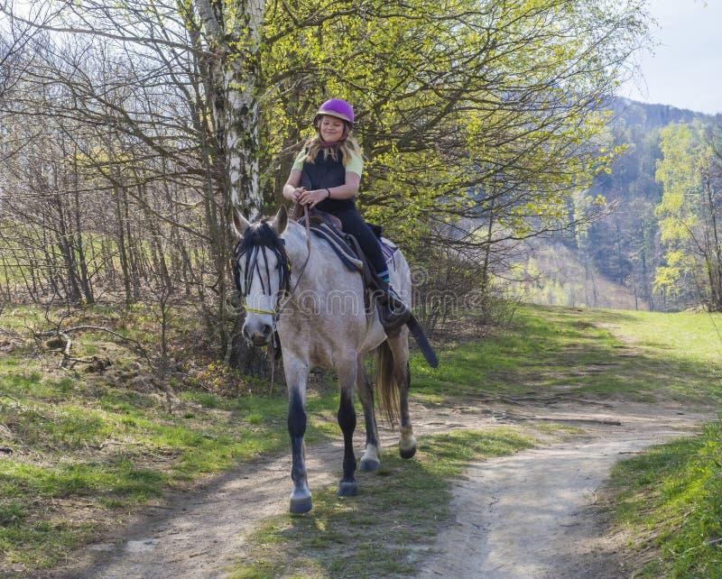 La repubblica Ceca, Hejnice, il 20 aprile 2019: Giovane guida sorridente bionda della ragazza sul cavallo bianco in una foresta s fotografia stock