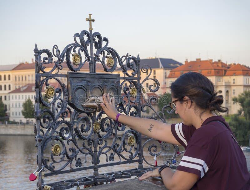 La repubblica Ceca, Praga, l'8 settembre 2018: Turista della giovane donna che tocca il sacerdote di caduta Saint John di Nepomuk immagini stock