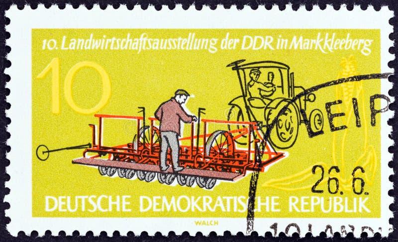 LA REPUBBLICA DEMOCRATICA TEDESCA - CIRCA 1962: Un bollo stampato in Germania mostra la Mais-piantatura della macchina, circa 196 fotografia stock libera da diritti