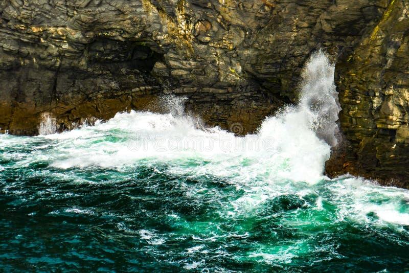 La resaca azulverde que truena se estrella contra los acantilados rugosos de Kilkee, península de la cabeza de lazo, condado Clar imagen de archivo