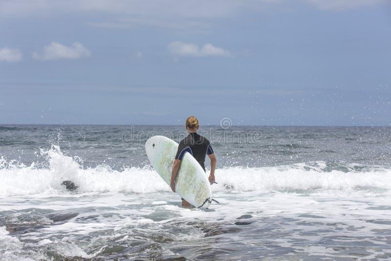 La resaca entra en el agua Persona que practica surf de sexo masculino que entra en el mar con su tablero en un traje que practic imágenes de archivo libres de regalías