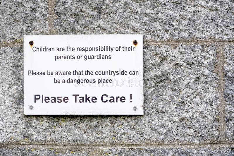 La responsabilidad de los niños de padres que el campo es lugar peligroso toma por favor la muestra del cuidado foto de archivo