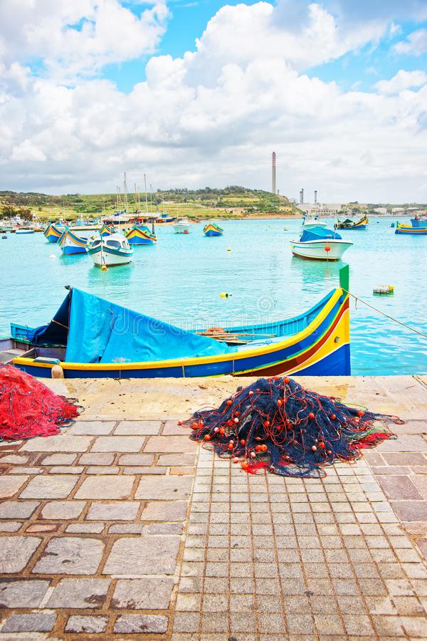 La rete da pesca e Luzzu hanno colorato le barche al porto Malta di Marsaxlokk fotografia stock