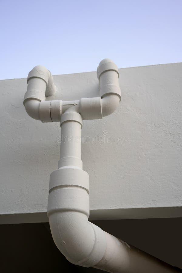 La rete di tubazioni dell'acqua installa con sul muro di cemento bianco immagini stock