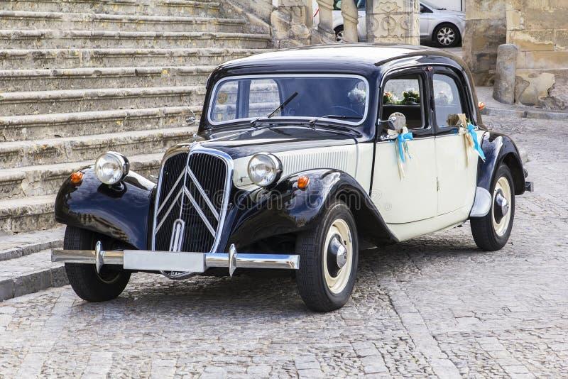La retro automobile del fondo attende le persone appena sposate all'entrata alla chiesa a Jerez de la Front immagine stock libera da diritti