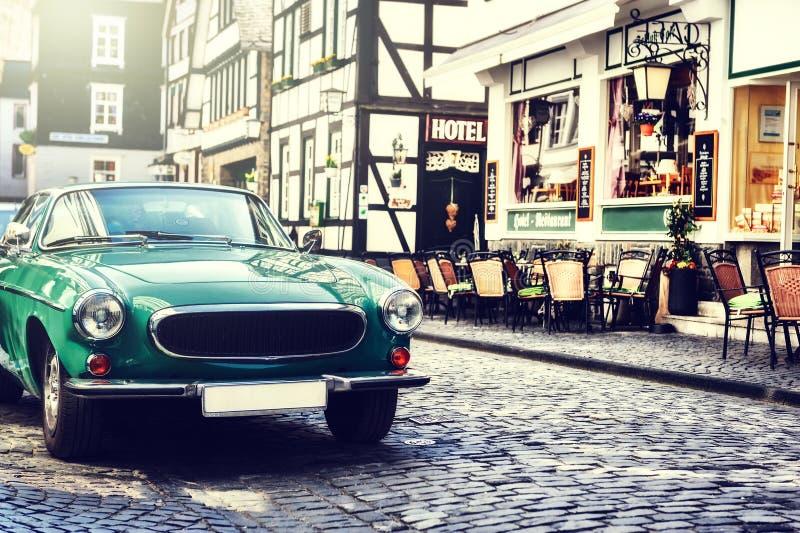 La retro automobile ha parcheggiato in vecchia via europea della città immagine stock