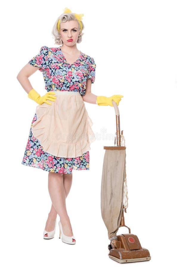 La retro casalinga infelice, con l'aspirapolvere d'annata, ha isolato la o immagine stock libera da diritti